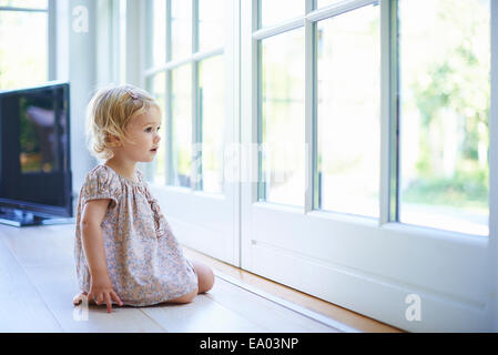 Portrait female toddler sitting on floor looking out of patio doors - Stock Photo