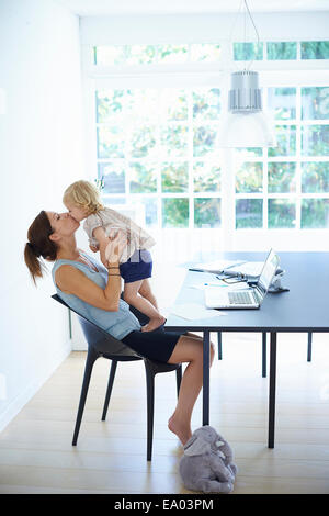 Mid adult woman holding up and kissing toddler daughter - Stock Photo