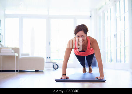 Mid adult woman doing press ups in living room - Stock Photo