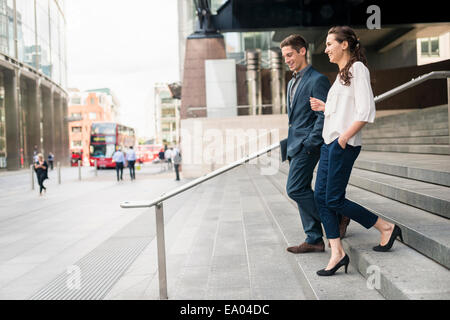 Rear view of young businessman and woman chatting whilst walking down stairway, London, UK - Stock Photo