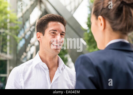 Young businessman and woman chatting at Broadgate Tower, London, UK - Stock Photo