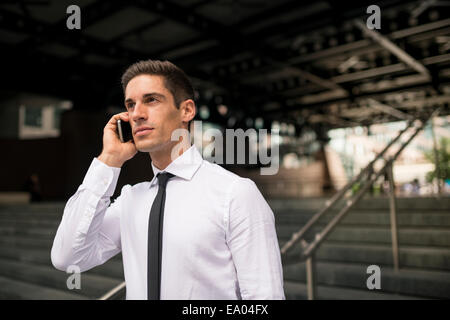Young businessman outside station chatting on smartphone, London, UK - Stock Photo