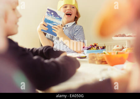 Young boy holding up opened Christmas present at table - Stock Photo