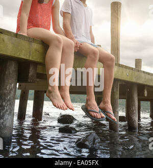 Young couple holding hands together and sitting on edge of jetty over lake - Stock Photo