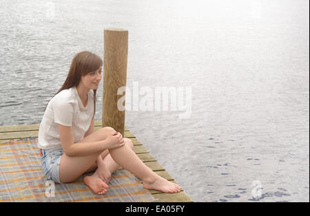 Young woman sitting at the end of a lakeside jetty - Stock Photo