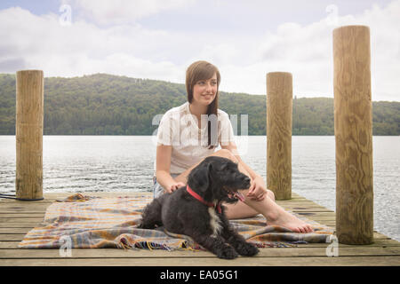Young woman sitting with pet terrier at the end of a lakeside jetty - Stock Photo