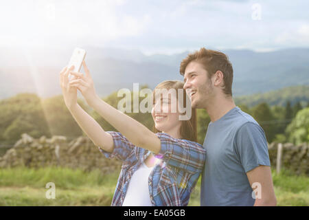 Young couple taking self portrait on mobile phone in countryside under sunny sky - Stock Photo