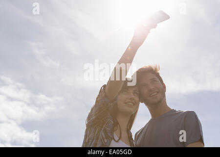 Young couple taking self portrait on mobile phone under bright sunny sky - Stock Photo