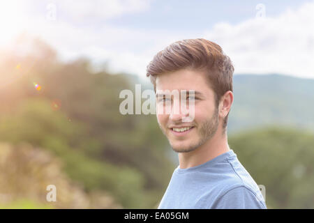 Portrait of young man smiling under bright sunlight - Stock Photo