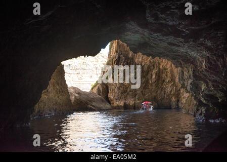 Tourist boat in the Blue Grotto sea caves in Malta - Stock Photo