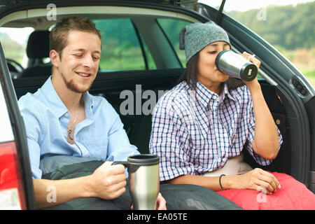 Couple sitting at rear of car with legs tucked in sleeping bag - Stock Photo