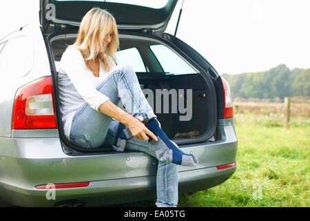 Woman sitting at rear of car putting on socks - Stock Photo