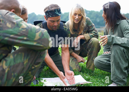 Paintball players preparing and planning game - Stock Photo