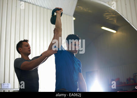 Trainer coaching man with kettlebell in gym