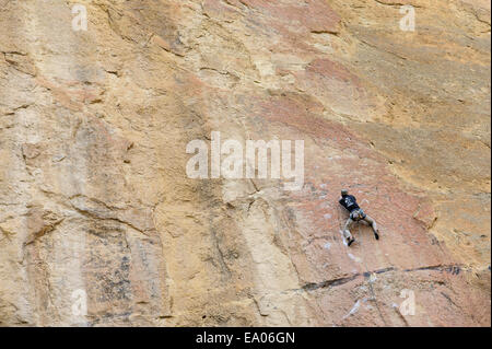 A rock climber ascends a cliff at Smith Rock in Oregon, USA - Stock Photo