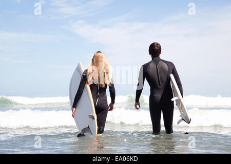 Young couple walking out to sea holding surfboards, rear view - Stock Photo