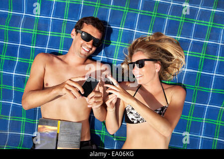 Young couple lying on beach towel using smartphones - Stock Photo