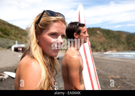Young couple standing on beach looking out to sea - Stock Photo