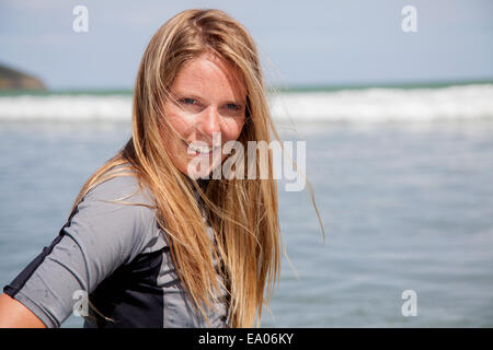 Portrait of young woman wearing wetsuit - Stock Photo