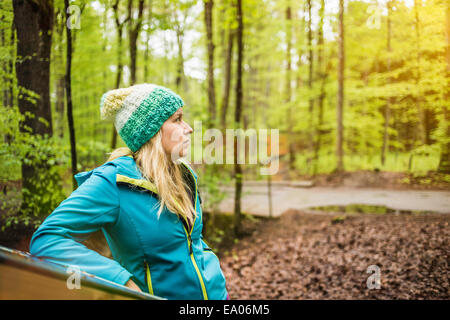Young woman standing in forest looking away - Stock Photo