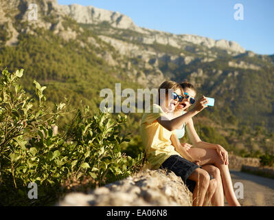 Brother and sister making faces for selfie on smartphone, Majorca, Spain - Stock Photo