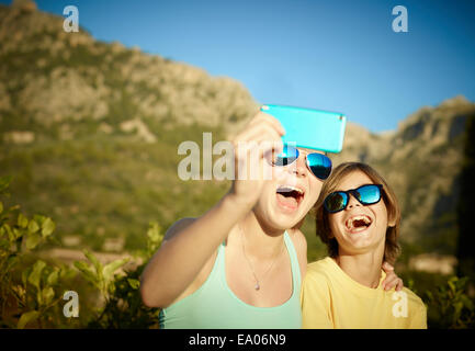 Sister and brother making faces for selfie on smartphone, Majorca, Spain - Stock Photo
