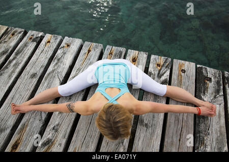Overhead view of mid adult woman with arms and legs outstretched practicing yoga on wooden sea pier - Stock Photo