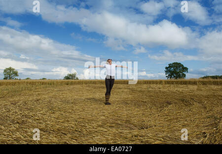 Mature female farmer celebrating with arms open in harvested wheat field - Stock Photo