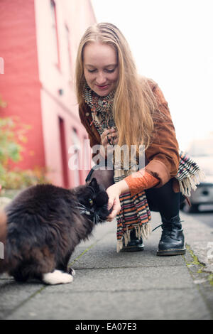 Young woman petting black cat on pavement - Stock Photo