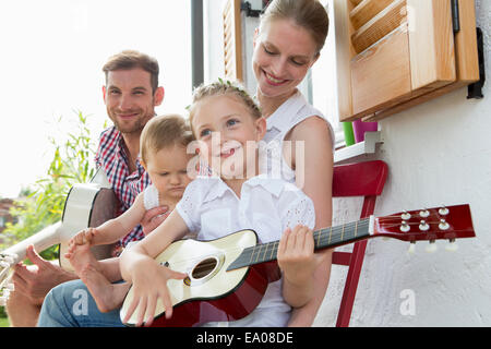 Girl playing guitar with family - Stock Photo