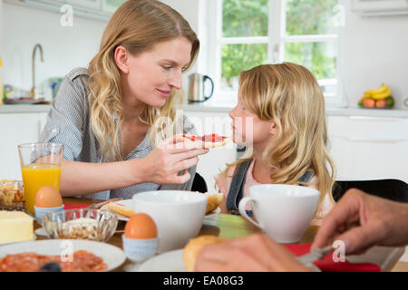 Mother offering daughter some food - Stock Photo