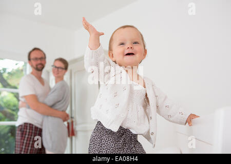 Baby with hand raised, parents in background - Stock Photo