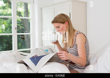 Mid adult woman sitting in bed reading newspaper - Stock Photo