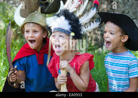 Three children wearing fancy dress costumes, playing in park - Stock Photo
