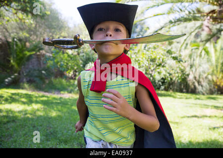 Young boy wearing fancy dress costume, running in park - Stock Photo