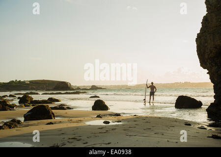 Mature man standing at waters edge holding surf board - Stock Photo