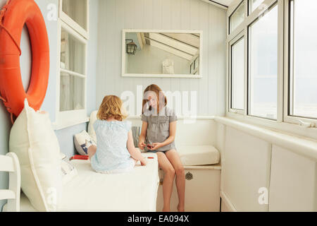 Two sisters playing cards in holiday apartment porch - Stock Photo