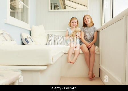Portrait of two sisters sitting in holiday apartment porch - Stock Photo