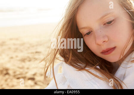 Close up portrait of girl wrapped in blanket on beach - Stock Photo