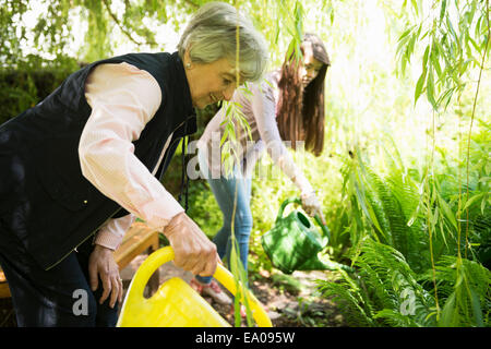 Grandmother and granddaughter watering plants under willow tree - Stock Photo