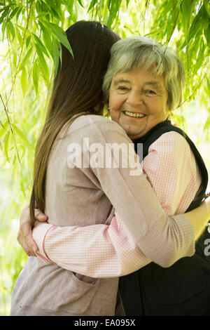 Grandmother and granddaughter under willow tree - Stock Photo