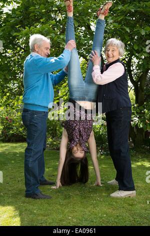 Grandparents and granddaughter doing acrobatics in garden - Stock Photo