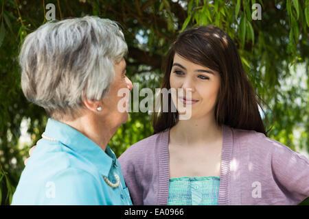 Grandmother and granddaughter having conversation in garden - Stock Photo