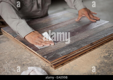 Carpenter smoothing surface of wood plank with sandpaper in factory, Jiangsu, China - Stock Photo