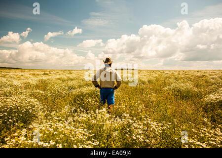 Man on field of wild flowers, Sarsy village, Sverdlovsk region, Russia - Stock Photo
