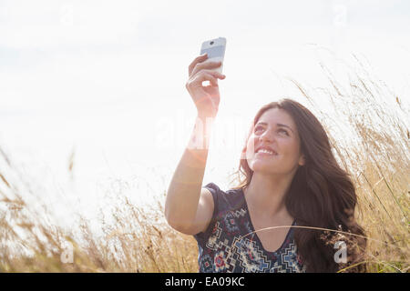 Young woman taking selfie with smartphone in field