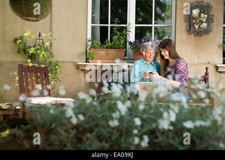 Young woman listening to music with grandmother - Stock Photo