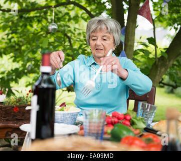 Senior woman serving salad - Stock Photo