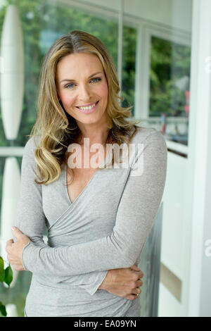 Mature blonde woman smiling, portrait - Stock Photo