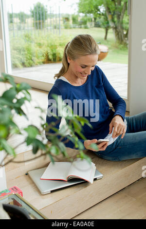 Mature woman using cell phone - Stock Photo